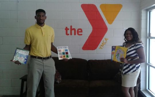 Junior Matrell Smith and senior Christen Hyde dropping off some books from the NABJ Book Drive held at Stillman College at the Benjamin Barnes YMCA. Photo by Victor Christian.