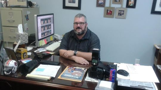 Arthur McLean, general Manager, editor and photographer of the Thomasville Times newspaper, poses for a picture at his desk. Photo by Christen Hyde.